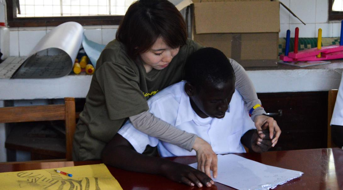 A Projects Abroad volunteer doing a physiotherapy internship in Ghana helps a young student to recover movement in his arms and hands.